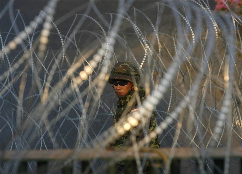 A soldier stands guard among a barricade at the Public Health Ministry in Nonthaburi province on the outskirts of Bangkok