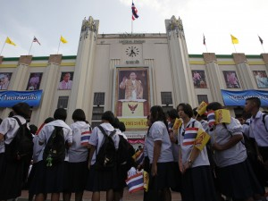 Students stand in front of a portrait of King Bhumibol Adulyadej in Bangkok